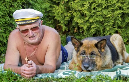 A cheerful elderly retired man and a German shepherd with glasses lie side by side on a blanket in a rural garden. Summer in Sunny weather. Stock Photo