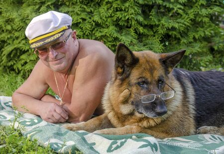 An elderly pensioner and a German shepherd with glasses lie side by side on a blanket in a rural garden. Summer in Sunny weather.