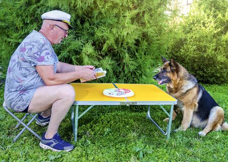 An elderly pensioner reads a magazine with a German shepherd sitting at a table in the countryside in the garden, summer in Sunny weather. Stock Photo