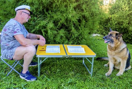 An elderly pensioner is reading a magazine and talking to a German shepherd, sitting at a table in nature in the garden, in summer in Sunny weather. Stock Photo - 140901641