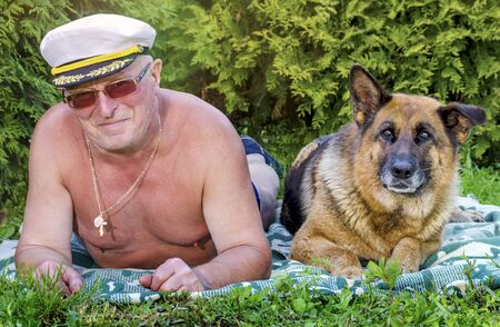 An elderly pensioner with a cheerful smile and a German shepherd dog lie next to each other on the grass in a rural garden. Summer in Sunny weather. Stock Photo