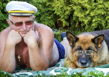 An elderly pensioner looks at a German shepherd with glasses lying next to him on a blanket in a rural garden. Summer in Sunny weather. Stock Photo