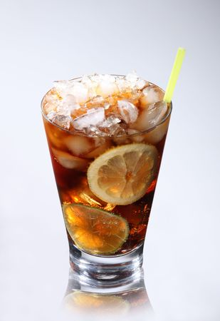 Glass with cola and ice on gray background