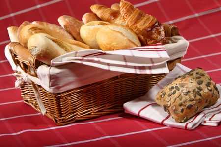 Baked goods in the basket on red tablecloth photo