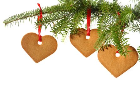 Gingerbread hearts hanging under fir branch and isolated against white background Stock Photo