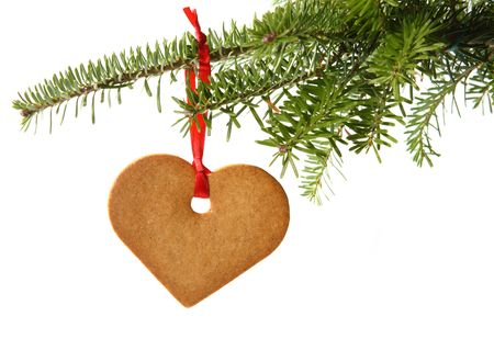 Gingerbread heart hanging under fir branch and isolated against white background Stock Photo