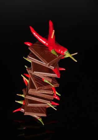 Chocolate with red chili pepper on black background Stock Photo