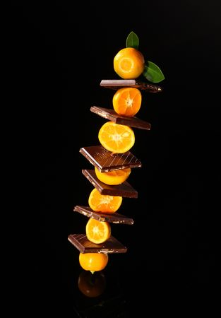 Chocolate with orange mandarin on black background