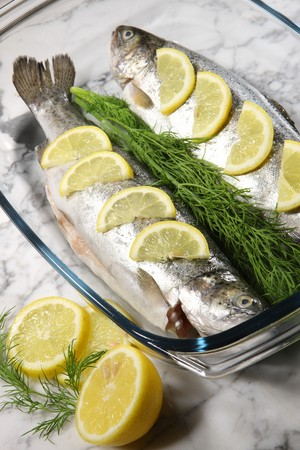 fish on a white plate with lemons and dill on stone  Stock Photo