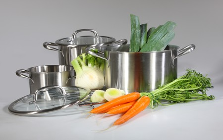 Stainless steel pots and pans isolated on gray background  Stock Photo