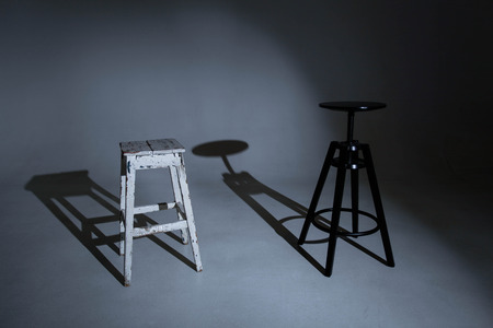 White stool and black portrait chair on a white, unlit chiclorama