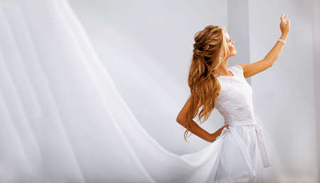 The girl is blonde, with a beautiful hairstyle and long hair in a wedding white dress. The hem of the dress crosses the frame, the woman reaches out for the light. Delicate and dynamic pose Archivio Fotografico
