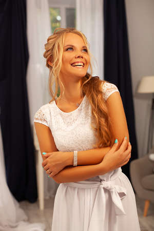 Bright and charming smile of a blonde with blue eyes. Emotion of joy and happiness. A young girl in a white dress laughs hugging herself with her arms. The photo of a beautiful girl is emotional.