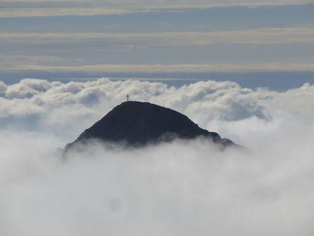 berg top in wolken met een kruis Stockfoto