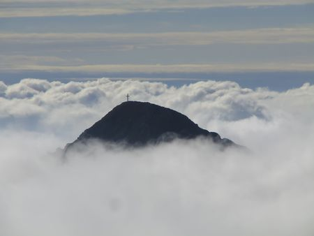 mountain top in clouds with a cross