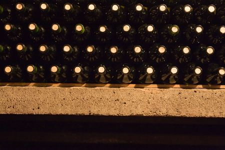 a stack of wine bottles in the shelf photo