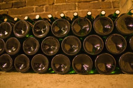 a close-up of stacked wine bottles in the cellar photo