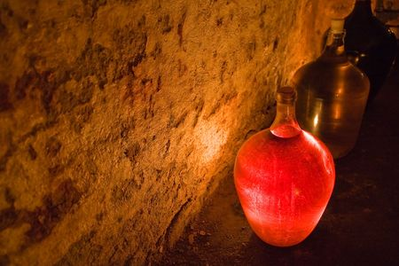 glass demijohn of rose wine lighten up by candle photo