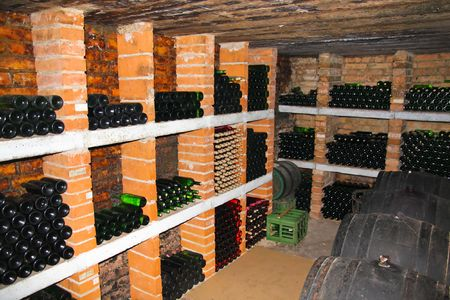 wine cellar witch stacked bottles and barrels photo