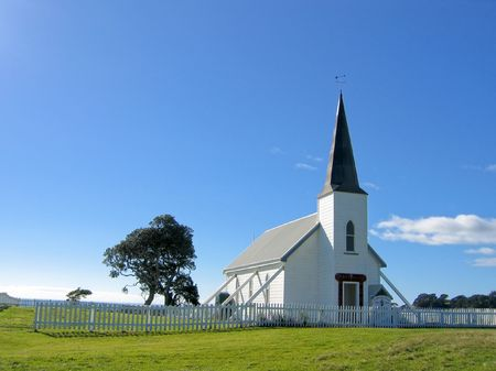 prayer tower: small white wooden protestant church with a blue sky