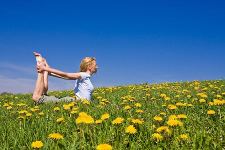 young female excercising yoga on flowery meadow photo