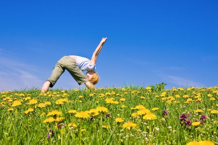 young female excercising yoga on flowery meadow Stock Photo - 3004707