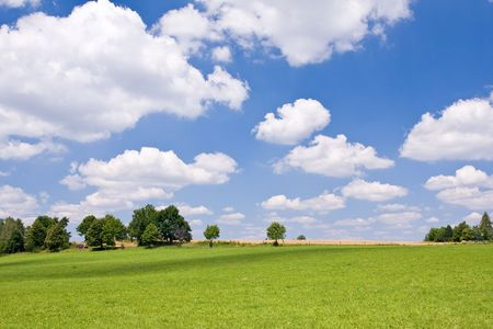 green farm land with a blue sky Stock Photo