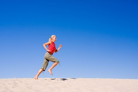 cloudless: beautiful female exercising on the sand dunes
