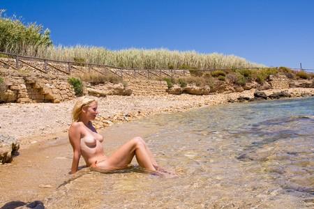naaktstrand: een mooie vrouw suntanning op het strand