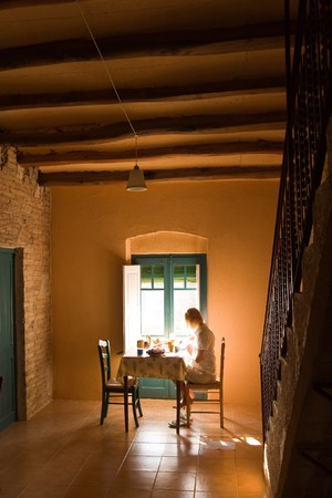 agriturismo: young female having breakfast indoor