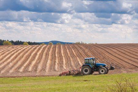 tractor planting potatoes in the springtime photo