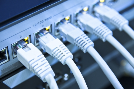 network cables: network cables RJ45 connected to a switch Stock Photo