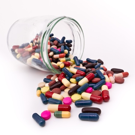 colorful tablets and capsules in glass container photo