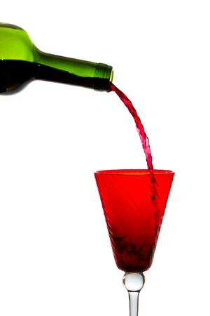 Verter el vino tinto en cristal aislado