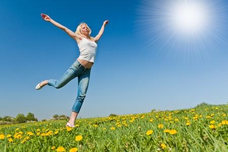 young female having fun on flowery meadow Reklamní fotografie