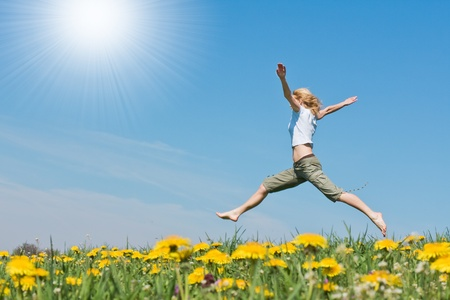 woman jumping: young female having fun on flowery meadow Stock Photo