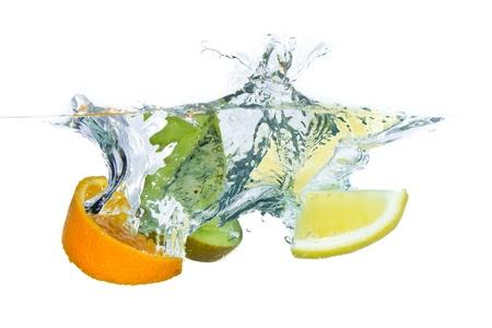 sliced citrus fruit with kiwi splashing isolated on white background photo