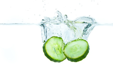 sliced cucumber splashing water isolated on white background