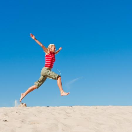 beautiful female exercising on the sand dunes photo