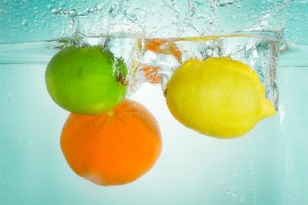 spruzzi acqua: limone e mandarino spruzzi d'acqua su sfondo bianco