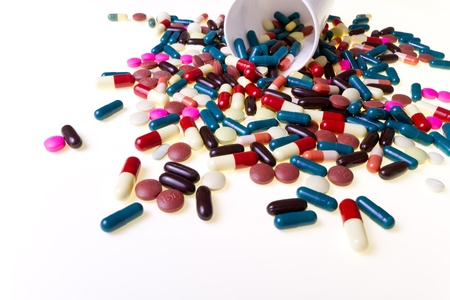 drug overdose: colorful pills spilling out of container, isolated