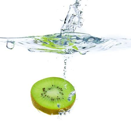 sliced kiwi fruit splashing isolated on white background