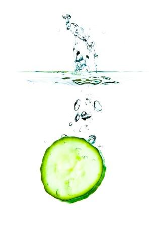 sliced cucumber splashing water isolated on white background photo