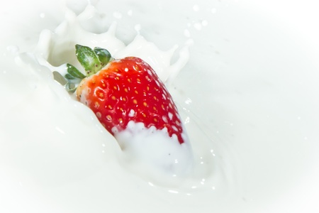 delicious fresh strawberry falling into splashing milk photo