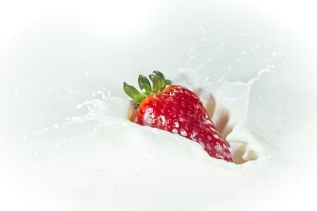 delicious fresh strawberry falling into splashing milk photo