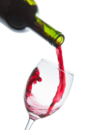 pour: red wine pouring into wine glass isolated Stock Photo