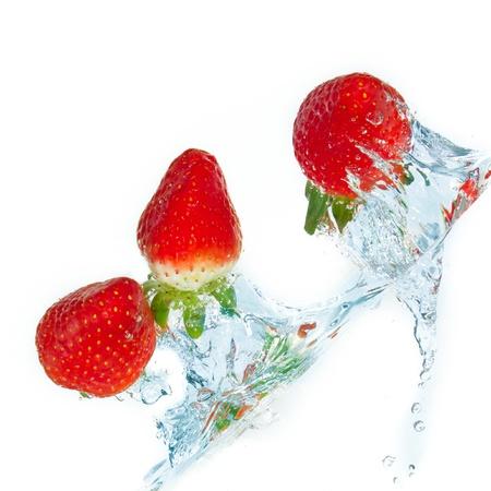 dropped: fresas frescas en agua con splash sobre fondos blancos Foto de archivo