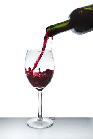 red wine pouring into wine glass isolated Stock Photo - 9651580