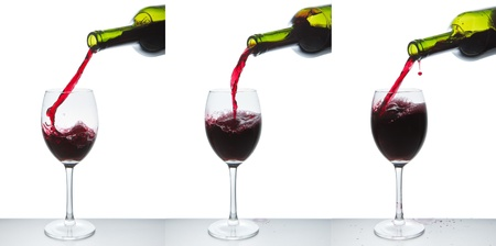 red wine pouring into wine glass isolated Stock Photo - 9824651