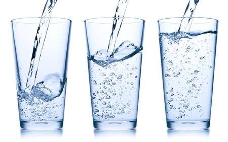 WATER GLASS: set di acqua versando in vetro su sfondo bianco Archivio Fotografico